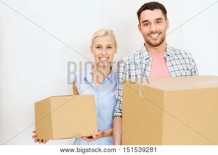 home, people, repair and real estate concept - happy couple holding cardboard boxes and moving to new place