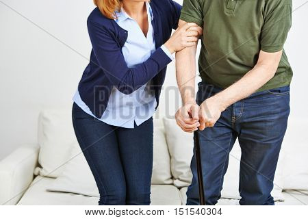 Woman supporting senior man with cane getting up from a sofa