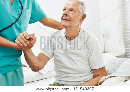 Geriatric caregiver helping old man getting up from bed
