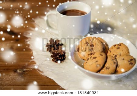 holidays, christmas, winter, food and drinks concept - close up of cups with hot chocolate or cocoa drinks and oat cookies on white fur rug