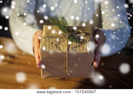 christmas, holidays, presents, new year and people concept - close up of woman hands holding gift box or parcel wrapped into brown mail paper and decorated with fir brunch