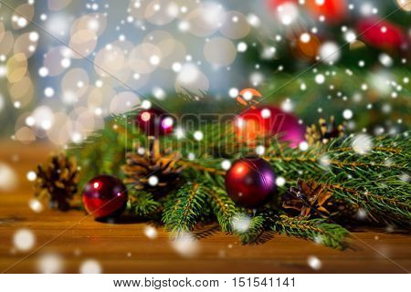 christmas decoration, holidays, new year and decor concept - close up of natural fir branch, ball and pinecone on wooden table