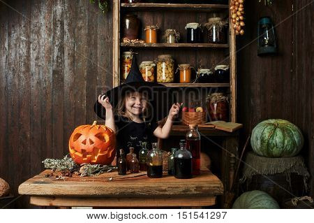 Little witch in a big black pointed hat and black dress fun about magic items
