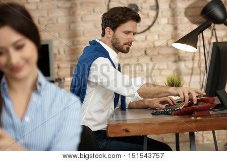 Businessman sitting at desk, using landline phone.