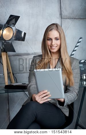 Happy young businesswoman using tablet computer, smiling.