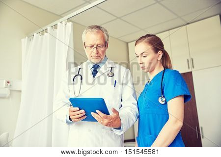 medicine, technology, health care and people concept - senior doctor and young nurse with tablet pc computer at hospital hospital ward