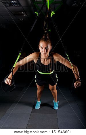 One women doing push ups training arms with straps Total Resistance eXercises fitness straps in the gym Concept workout healthy lifestyle sport