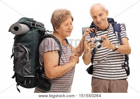 Senior hikers looking at a photograph on a camera isolated on white background