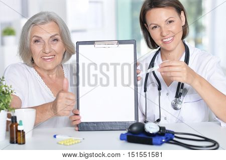 female doctor and her  senior patient  with folder