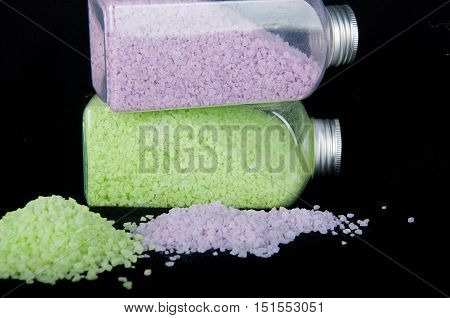 Two transparent plastic bottles with light purple green bath sea salt and heaps of grains on black background