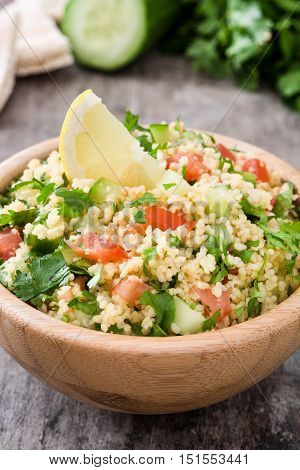 Tabbouleh salad with couscous in bowl on rustic wooden table