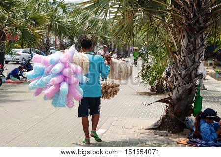 Pattaya Thailand - March 24 2016: Thai street vendor selling bread and cotton candy on a street. Walking hawker guy with lots of food from the back.