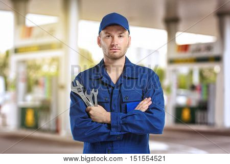 Young mechanic in uniform with crossed arms and wrenches standing on blurred petrol station