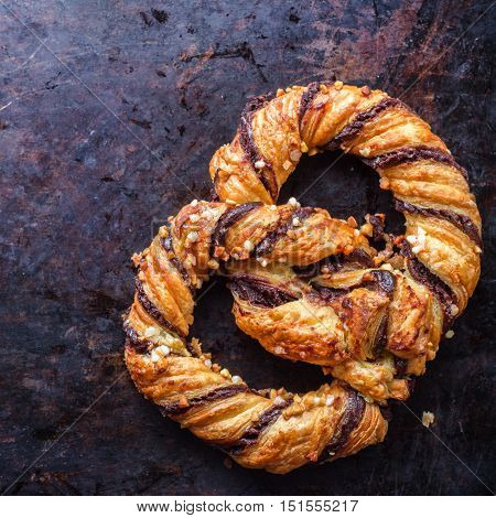 Homemade sweet pretzel with chocolate and crunchy almonds, traditional german bavarian treat on a black rusty table. Selective focus, top view overhead flat lay