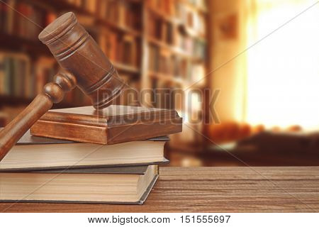 Gavel with sound block on bookshelf in library background