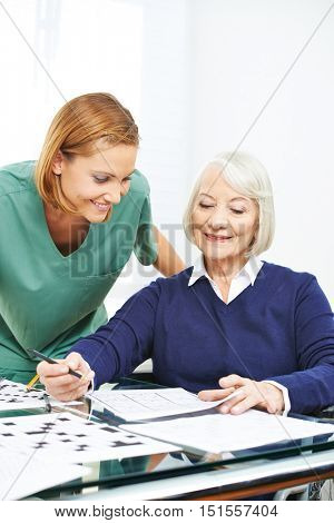 Senior woman doing memory training in nursing home
