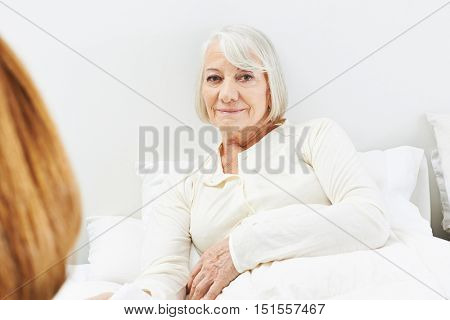 Old bedridden senior woman in nursing home laying in her bed