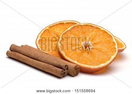 Slices of dried orange with cinnamon sticks isolated against white