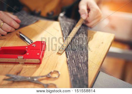 Man upholstering chair in his workshop measure wooden board