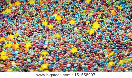 Sweet colorful confectionery sprinkling texture with yellow stars- sugar sprinkle dots, decoration for cake and bakery