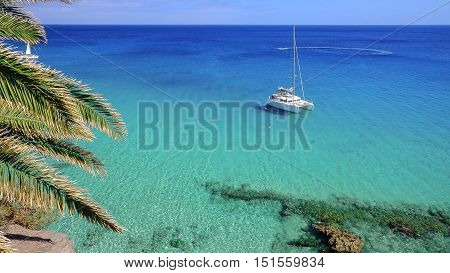 View on a white tourist boat in blue lagoon of Atlantic Ocean closed to the beach Playa de Morro Jable in Fuerteventura Spain.