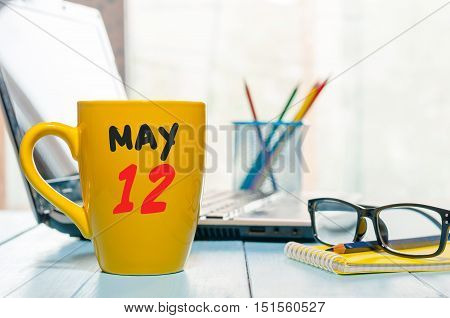 May 12th. Day 12 of month, calendar on morning coffee cup, business office background, workplace with laptop and glasses. Spring time, empty space for text.