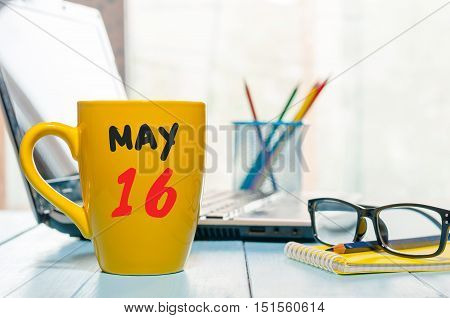 May 16th. Day 16 of month, calendar on morning coffee cup, business office background, workplace with laptop and glasses. Spring time, empty space for text.