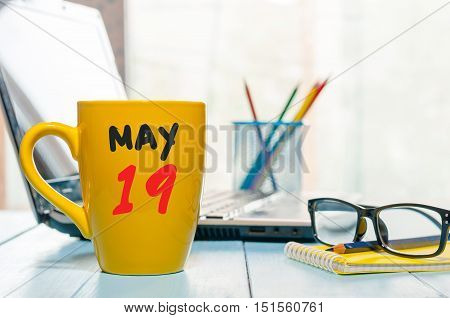 May 19th. Day 19 of month, calendar on morning coffee cup, business office background, workplace with laptop and glasses. Spring time, empty space for text.