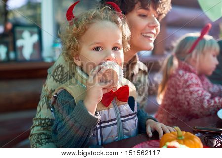 Little girl eating cake while sitting on her mother's knees