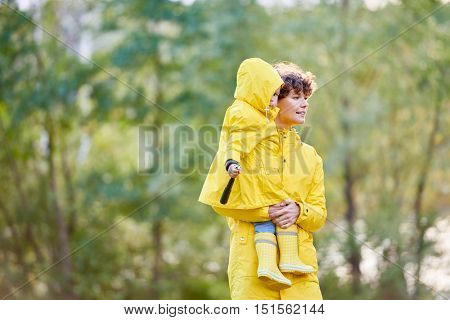 Mother walking with her daughter in raincoats