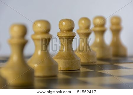 White wooden pawns standing in a row diagonally on a chessboard with white and black squares fields