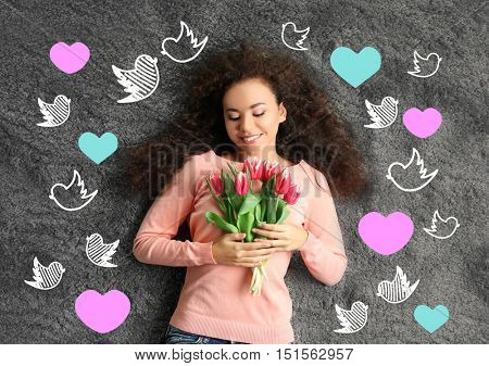 Beautiful young woman with bouquet. Colorful hearts and birds drawings on gray textured background.