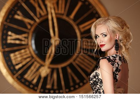 Elegant Lady With Makeup And Blond Hairstyle Posing In Front Of Wall Clock, Golden Colors. Beauty Fa