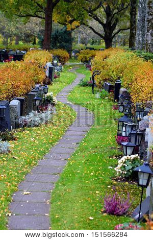 Path on cemetery. Tombstones on both sides of the path.