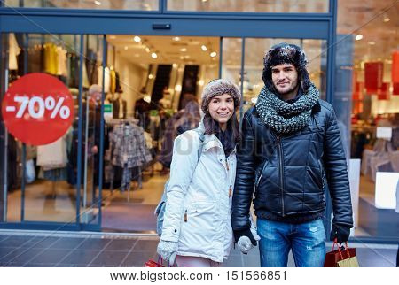 Young couple shopping at winter sale in the city.