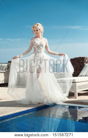 Beauty Portrait Of Bride Wearing In Wedding Dress With Voluminous Skirt Walking Near Swimming Pool O