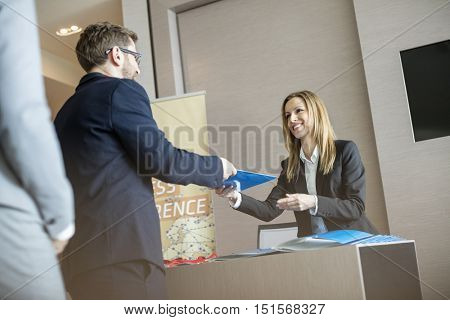 Happy receptionist giving file to businessman at convention center