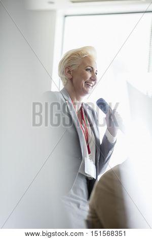 Happy businesswoman speaking through microphone during seminar