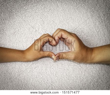 Mother and child made a heart with his hands on a light background. Adult and children's hands make a heart with your fingers.