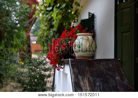 Rural House With Red Geranium Flowers In The Veranda