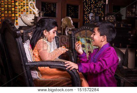 indian siblings eating laddu on diwali or festival, kids celebrating diwali festival with sweets