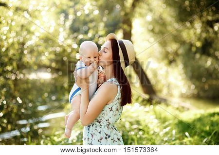 Preety Young mother in hat with newborn baby boy sunny nature background
