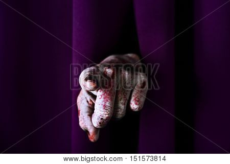 closeup of the scary bloody hand of an undead man or a monster pointing his forefinger at the observer, through a purple stage curtain