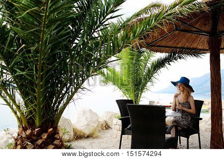 Pretty girl or woman with blond hair in hat drinks cocktail in sea beach cafe or bar under sun umbrella and palms on beautiful seascape