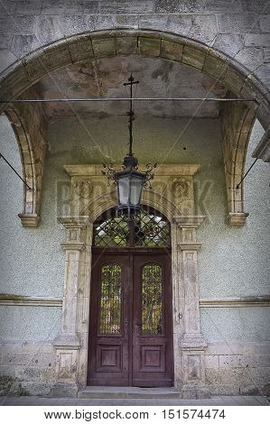 door in an old house with a lantern and a porch