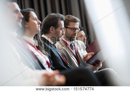 Businessmen discussing over file during seminar