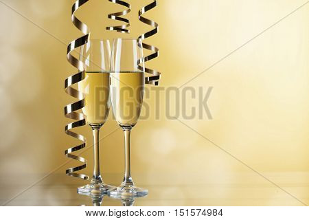 Two champagne glasses and curly ribbon party concept