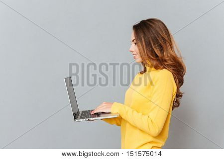 Side view portrait of a cheerful young woman typing on laptop isolated on a gray background