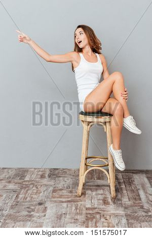 Amazed charming woman sitting on the chair and pointing away isolated on gray background