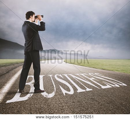 Businessman looks at the economic future with binoculars on the business road